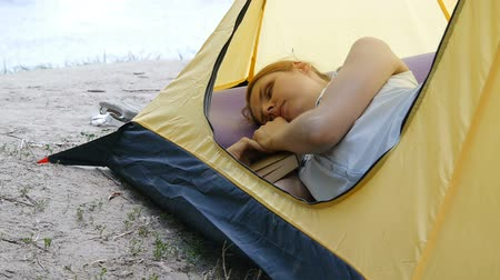 Young woman traveler sleeps in a tent. Tired hiker girl fell asleep with a book in a camping tent. Hiking, travel, green tourism concept. Healthy active lifestyle.
