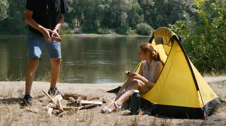 A man collects firewood for a fire near the tent. The girl sits in a tent and drinks tea. Hiking, travel, green tourism concept. Healthy active lifestyle. River and forest in the background.