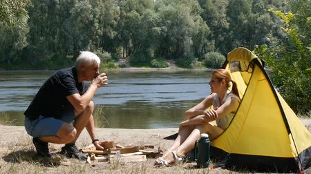 Young female traveler is sitting in the tent. The girl passes the man a cup of tea. The man drinks tea and laughs. Hiking, travel, green tourism concept. River and forest in the background.