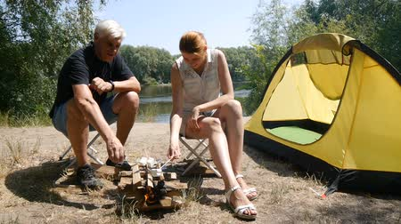 A man and a girl roasting marshmallows on a fire. Hiking, travel, green tourism concept. Healthy active lifestyle. River and forest in the background. Stok Video