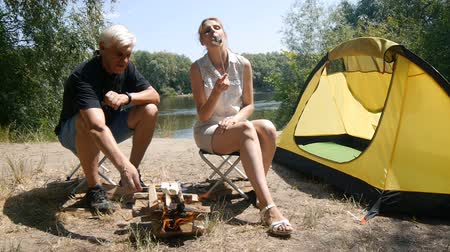 A man and a girl roasting marshmallows on a fire. Marshmallow ready. The girl eats marshmallows. Hiking, travel, green tourism concept. Healthy active lifestyle. River and forest in the background. Stok Video