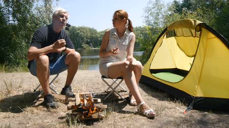 A man and a girl roasting marshmallows on a fire. A man and a girl eat marshmallows. Hiking, travel, green tourism concept. Healthy active lifestyle. River and forest in the background.