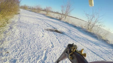 bigodes : The hunter retrieves the shot cartridges from the barrel and charges new ones. The fired shells are smoking. Winter hunting. First-person view. Stock Footage