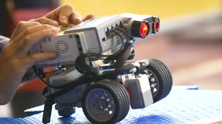 technics : Childs hand launches robot program.close-up.