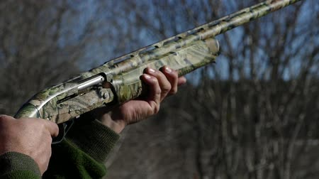 A camouflaged shotgun makes a shot. Cartridges fly out of the trunk. Skeet shooting. Slow motion.