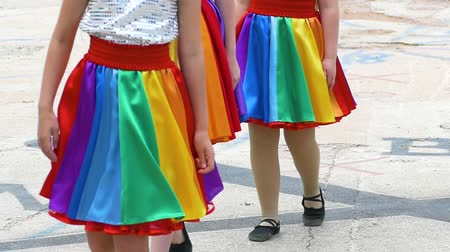 A team of young girls is dancing. Girls dance in the same rainbow suits. Rainbow skirt. Dostupné videozáznamy