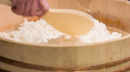 peeled grains : Look at this rice. Selective focus on Asian chef standing in kitchen of sushi bar mixing rice in big wooden bowl with help of wooden spoon preparing it for sushi rolls