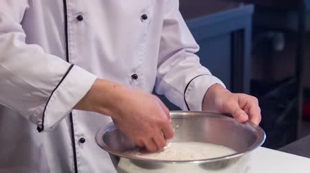 peeled grains : Look at this rice. Tracking shot of smiling Asian chef in white uniform standing in kitchen of sushi bar washing rice in big wooden bowl preparing it for sushi rolls Stock Footage