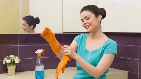 glove : My hands will be safe. Young pretty smiling woman standing in bathroom putting on orange gloves to begin tidying up