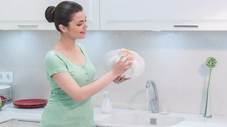 temizleme maddesi : Washing up is my favorite doing. Young happy net woman standing in kitchen near sink washing up and wiping white plates