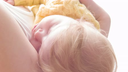 napfény : Sunny love. Close-up of baby sleeping on hands of its mother on sunny white background Stock mozgókép