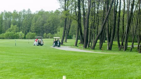 kurs : Driving to point. Shot of golf cars driving on field Wideo
