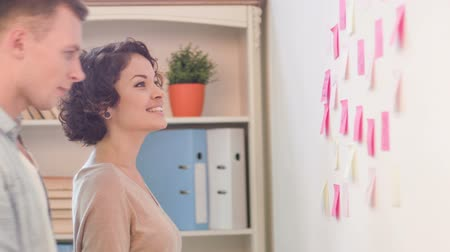 munkahelyek : Coworkers are attaching post-it notes to the wall. Stock mozgókép