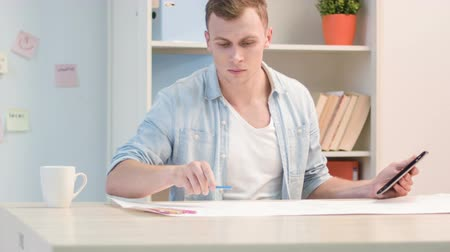 collaborator : Young workman is busy with checking the construction plan. Stock Footage