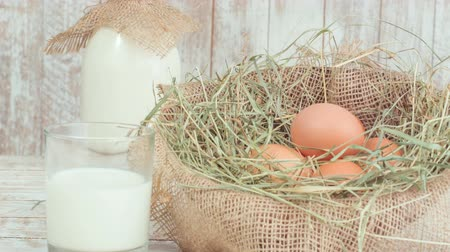 молочный : Milk and eggs in straw nest. Стоковые видеозаписи