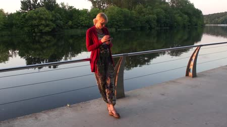 cômico : Young Woman Looking At Smartphone On Riverbank Stock Footage