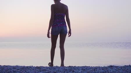 passo : Young woman going along a shore at sunrise
