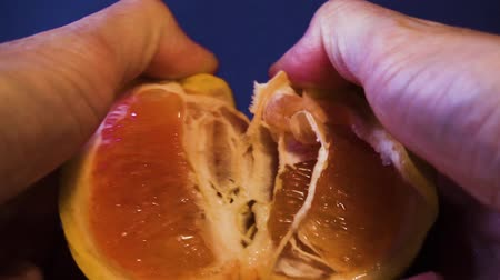 preslenmiş : Mans hands tearing a fresh juicy grapefruit. Close-up.