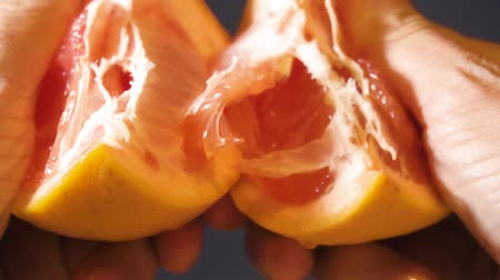 Mans hands tearing a fresh juicy grapefruit. Close-up.