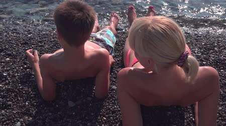 Young mother in bikini and her son sunbathing on a pebble beach Dostupné videozáznamy