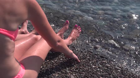 anne : Young mother in bikini and her son sunbathing on a pebble beach Stok Video