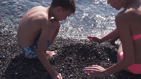 anne : Young slim mother and her son play with pebbles on beach, slow motion Stok Video