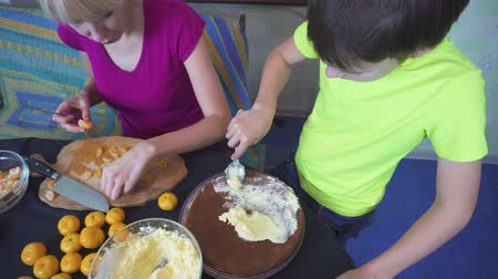 baking ingredient : Boy is helping his mother to cook a cake at home kitchen