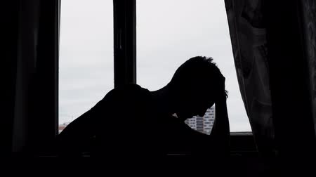 Silhouette of desperate sad man in the dark in front of a window