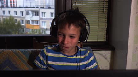 Teenage boy using his laptop computer at home, smiling and laughing, with earphones. Watching movies Dostupné videozáznamy