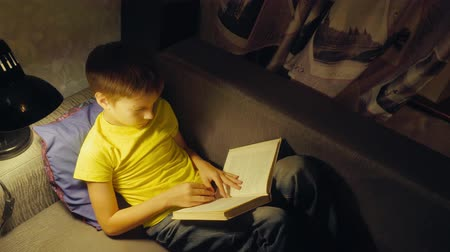 Boy reading a book on sofa at home in the evening Dostupné videozáznamy