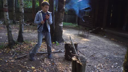 Boy chopping wood in the backyard. He prepares firewood. Steadicam shot.