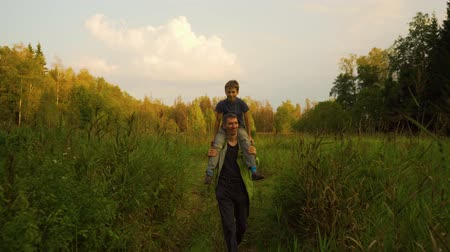 Father carrying his son on shoulders walking through forest and high grass before sunset in summer. Slow motion Dostupné videozáznamy
