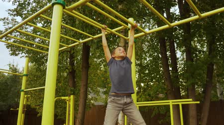 Boy exercising on a sports ground by his hands