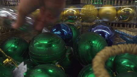 Christmas shopping. The guy is choosing the Christmas decorations. Man buying balls for a Christmas or New Year tree Dostupné videozáznamy