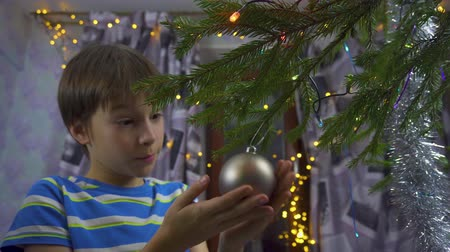 Boy decorating Christmas tree at home Dostupné videozáznamy
