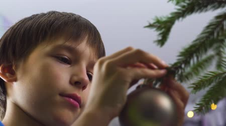 Boy decorating Christmas tree at home. Closeup.