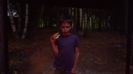 Cute boy appetizing bites sandwich by their house in woods during summer vacation