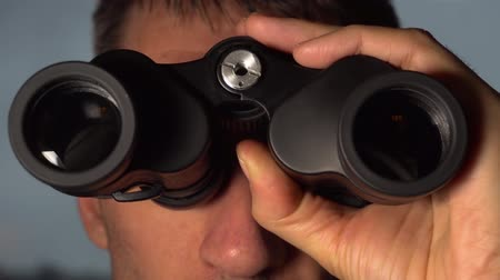 hidden face : Man looks and searches with binoculars Stock Footage