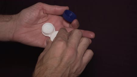 soczewki kontaktowe : Man taking contact lens from storage case, visual impairment. Close-up of hands.
