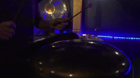 chime : Woman is playing meditative instrument tank drum in a dark meditation room.