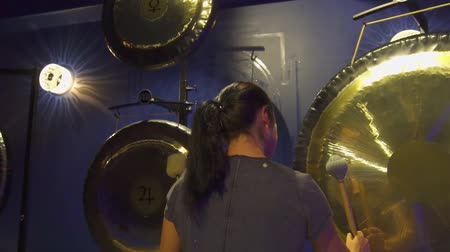gong : Woman is playing a big gong with a special beater in a meditation room.