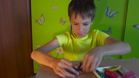 Çocuk bakımı : Boy is sitting at the desk and sculpting figures with colored plasticine. Development of fine motor skills Stok Video