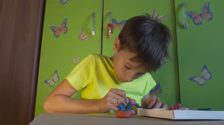 plastelíny : Boy is sitting at the desk and sculpting figures with colored plasticine. Development of children fine motor skills