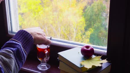 ароматический : Mans hand stirring a cup of tea in front of the window in autumn