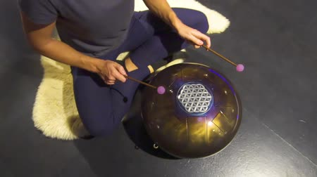 percussão : Woman is playing meditative instrument tank drum in a dark meditation room.