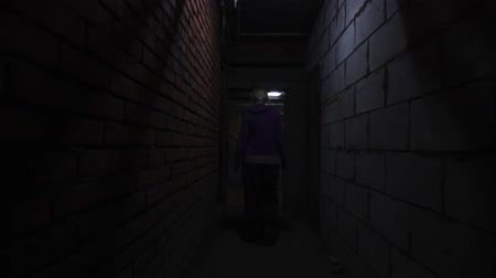 бункер : Woman moving in dark gloomy basement corridor Стоковые видеозаписи