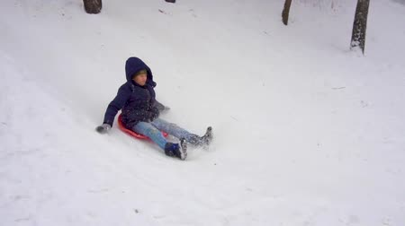 new town : Boy riding a show hill. Winter fun. Slow motion Stock Footage