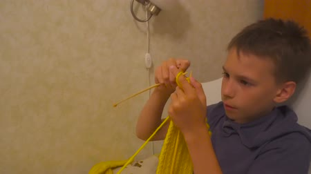 かぎ針編み : Boy is knitting a scarf with knitting needles. Learning how to knit. Homework 動画素材
