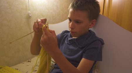 tanımlayıcı : Boy is knitting a scarf with knitting needles. Learning how to knit. Homework Stok Video