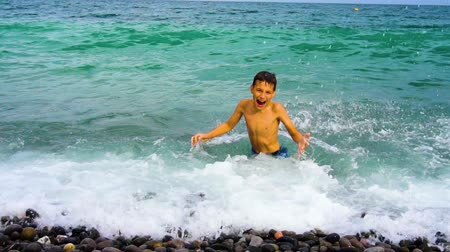 eleven people : Boy having fun on beach, slow motion. Family at pebble seashore in summer.